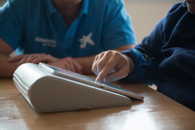 """Voluntaria """"la Caixa"""" forma a una persona en el uso de tablets para comunicarse con sus familiares."""